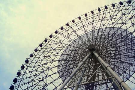 a big ferris wheel on the cloudy sky