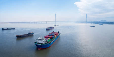 Foto de container ships waiting to enter port at anchor on yangtze river with jiujiang cable-stayed bridge , water transport concept - Imagen libre de derechos