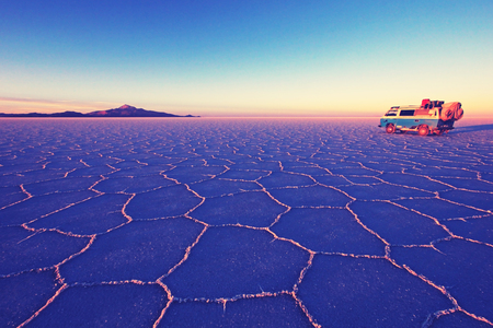 Old german vintage campervan on Salar de Uyuni, salt lake, is largest salt flat in the world, altiplano, Nashville retro vintage photo filter effect, warm color temperature, increased exposure and lower contrast, Bolivia, South America