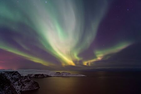Photo pour Intense northern lights, Aurora Borealis over Knivskjelloden Island, view from Nordkapp, North Cape, the most northern point of Europe, Finnmark, Norway - image libre de droit