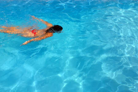 Girl swimming underwater in a clear water swimming pool