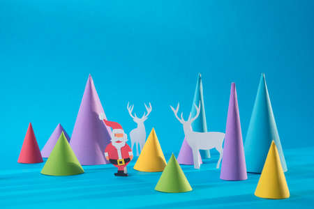 Christmas handmade 3d paper cut santa with deers and colorful pine tree shapes. Ideal for xmas greeting card, holiday poster or web.