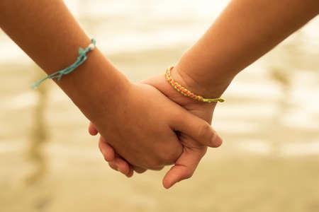 Foto de Close up of two children holding hands on the beach sand, summertime friendship concept. - Imagen libre de derechos
