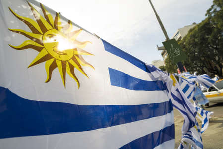 Photo pour Uruguayan flag in Montevideo city street market background. Uruguay country national emblem. - image libre de droit