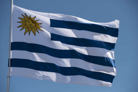 Photo pour Uruguayan flag waving in the wind on blue sky background. Uruguay country flagpole with national emblem. - image libre de droit