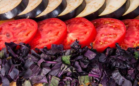 Sliced eggplant tomato and basil leaves horizontally isolated on white background