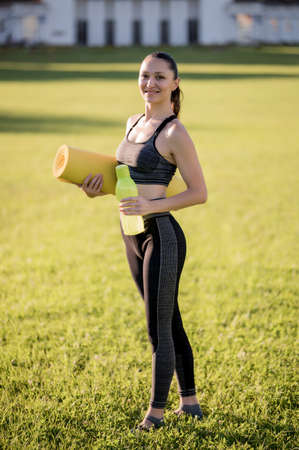 Photo for Beautiful young woman while wearing a tight sports outfit holding a yellow mattress and a bottle of water in hand, poses in the park before doing pilates or yoga exercises - Royalty Free Image