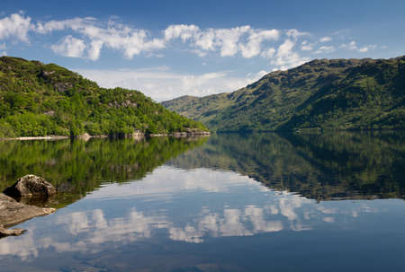 Reflections of treed and clouds on Loch Lomond, Scotland, United Kingdom