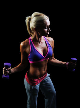 Beautiful muscular woman exercise on a black background
