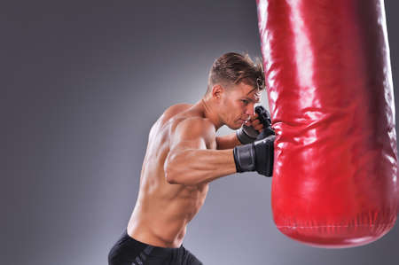 Photo pour Muscular Fighter Practicing Some Kicks with Punching Bag. Boxing on Gray Background. The Concept of a Healthy Lifestyle - image libre de droit