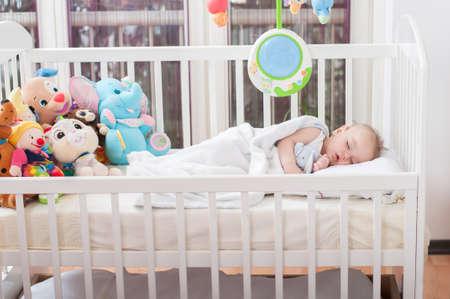Foto de Beautiful baby boy laying down in his bed and sleeping - Imagen libre de derechos
