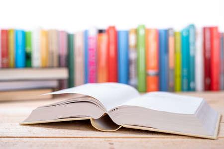 Photo pour Close-up open book with library bookshelf toned background - image libre de droit