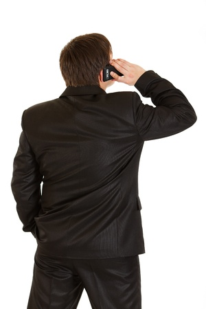Businessman standing  back to camera and talking on mobile phone isolated on white