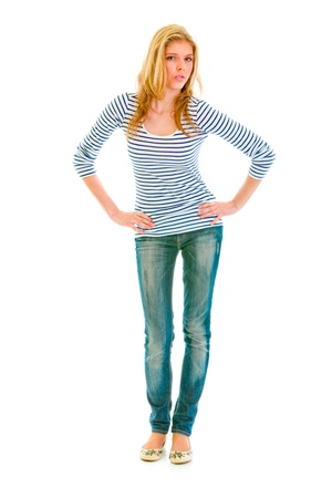 Full length portrait of beautiful teen girl with hands on hips attentively looking at you isolated on white