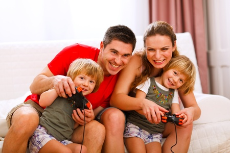 Mom and dad playing with twins daughter on console