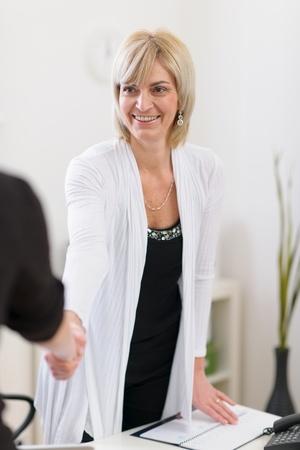 Smiling senior business woman shaking visitors hand