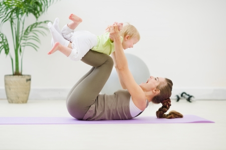 Photo for Healthy mother and baby making gymnastics - Royalty Free Image