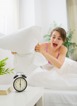 Angry woman trying to break alarm clock by pillow