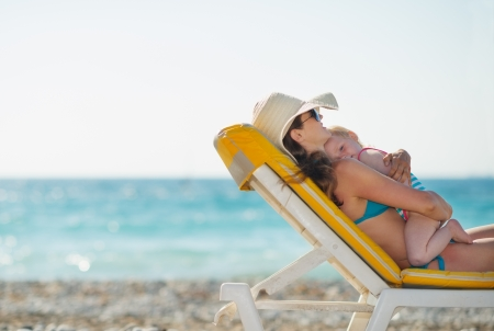 Photo for Mother with baby laying on sunbed on beach - Royalty Free Image