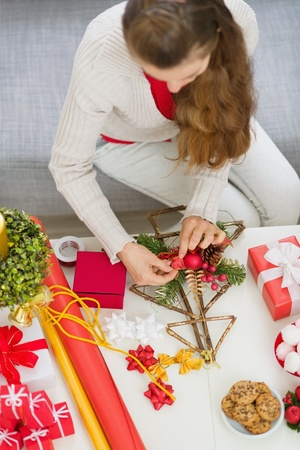 Closeup on table where female making Christmas decorations. Upper view