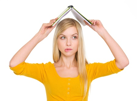 Confused student girl with raised book over head