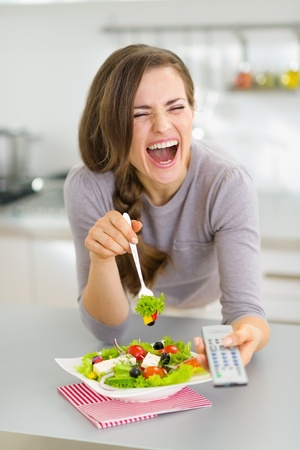 Laughing young woman eating salad and watching tv in kitchen