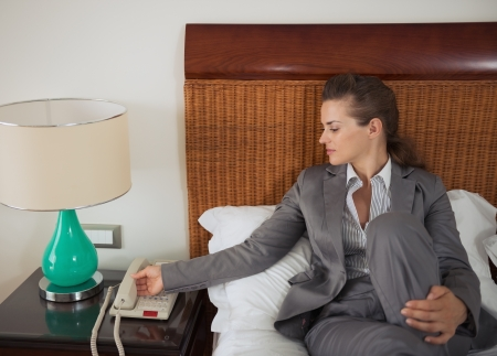 Business woman answering phone call on bed in hotel room