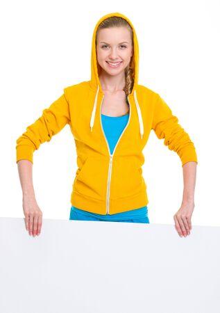 Happy teenager girl showing blank billboard
