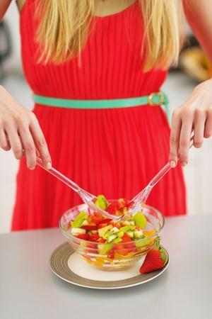 Closeup on young woman mixing fresh fruits salad