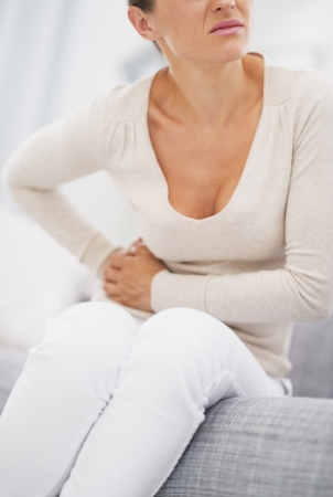 Closeup on young woman having stomach pain
