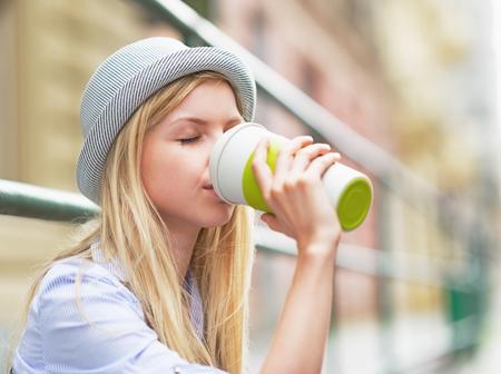 Hipster girl drinking hot beverage on city street