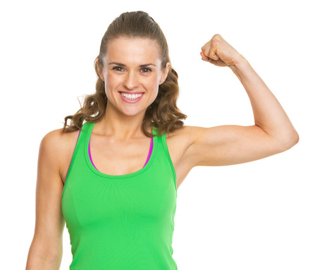 Smiling fitness young woman showing biceps