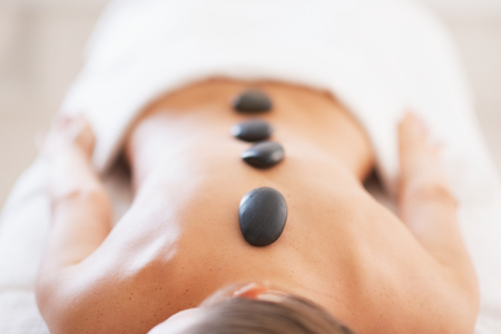 Closeup on relaxed young woman receiving hot stone massage