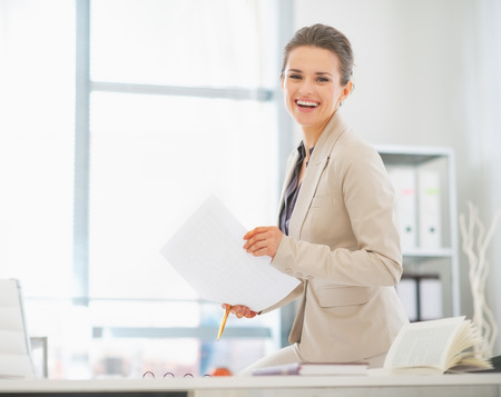 Happy business woman working in office with documents