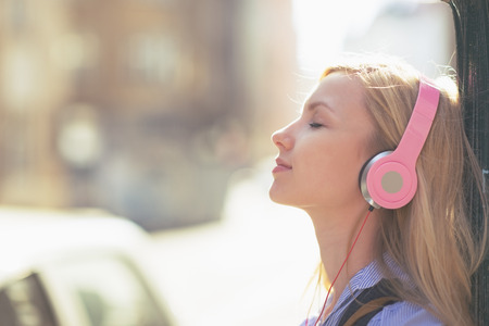 Young woman listening music in headphones in the city