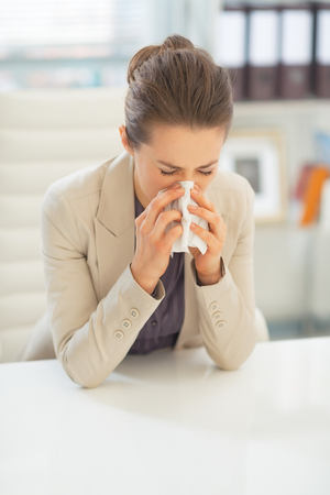 Business woman in office blowing nose
