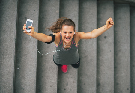Photo for Portrait of happy fitness young woman with cell phone outdoors in the city rejoicing - Royalty Free Image