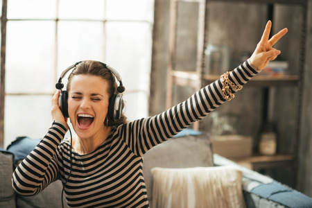 Photo pour Cheerful young woman listening music in headphones in loft apartment - image libre de droit