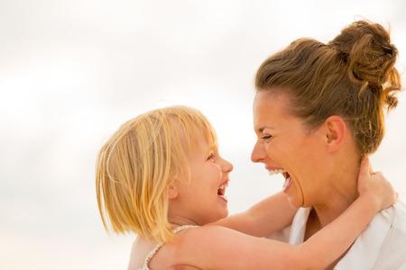 Foto de Portrait of laughing mother and baby girl hugging on beach at the evening - Imagen libre de derechos