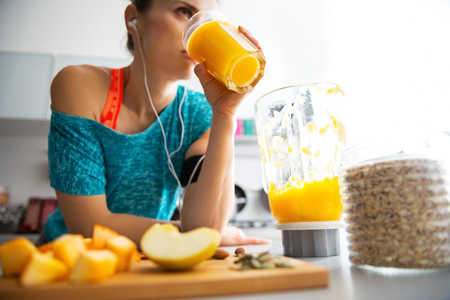 Close-up on fitness young woman drinking pumpkin smoothie in kitchen