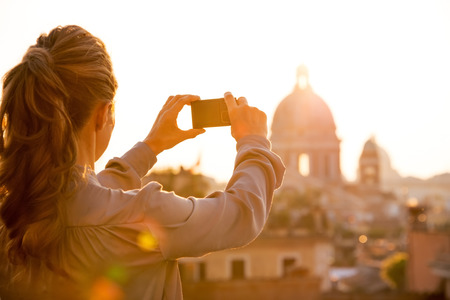 Young woman taking photo of rome panorama on sunset. rear view