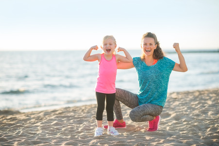 Foto de Healthy mother and baby girl showing biceps on beach - Imagen libre de derechos