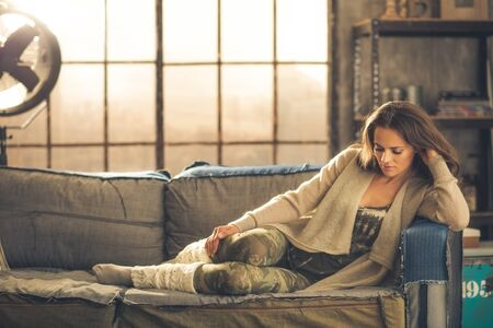 An elegant brunette woman wearing comfortable, casual clothing, leggings, and a cardigan is relaxing on a sofa in a loft. Sunlight shines through the window. Cozy atmosphere, industrial chic.