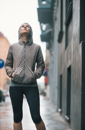 An athletic woman in workout and rain gear is looking up at the sky doubtfully, wondering if the rain will ever stop...