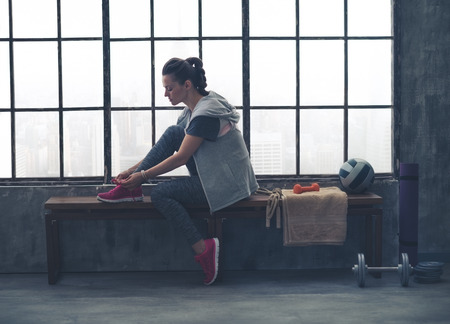 Foto de A quiet moment to tie her shoes. A fit, sporty young woman has one foot up on a bench, tying her shoelaces, as she gets ready to start her workout. - Imagen libre de derechos