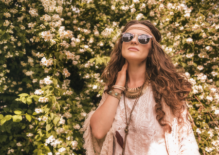 Longhaired hippy-looking young lady in knitted shawl and white blouse standing among flowers