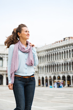 Strolling through St. Mark's Square in Venice, an elegant tourist holds her scarf as she makes her way through an almost-empty square. What an amazing feeling to have it virtually all to herself.