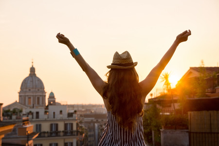 Foto de Seen from behind, a woman is standing with outstretched arms, looking out at the city of Rome at sunset in summer. - Imagen libre de derechos