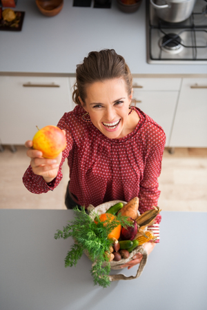 Take a bite, I promise it is delicious... An elegant woman is laughing and teasing in a kitchen, holding up colourful apple and cradling a burlap sac of fresh fall vegetables bought at the market.