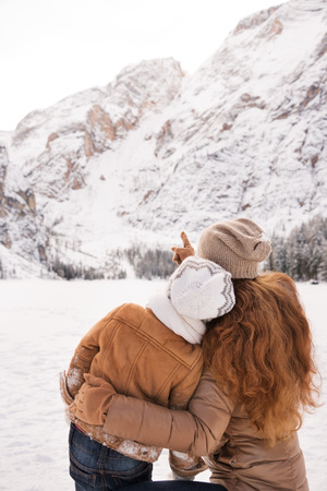 Winter leisure time spent outdoors among snowy peaks can turn the holidays into a fascinating journey. Seen from behind mother pointing child on snow-capped mountains